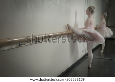 Beautiful ballerina warming up with the barre in the dance studio - stock photo