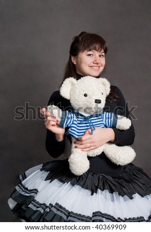 beautIFUL ballerina with bear in striped shirt on grey background