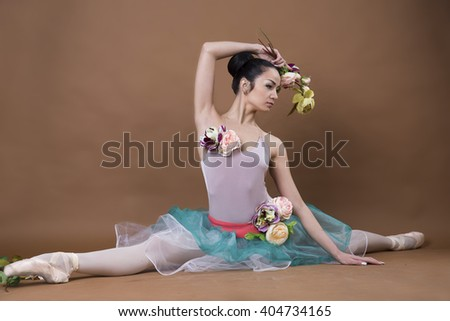 Beautiful ballet-dancer in dress with flowers posing on studio background - stock photo
