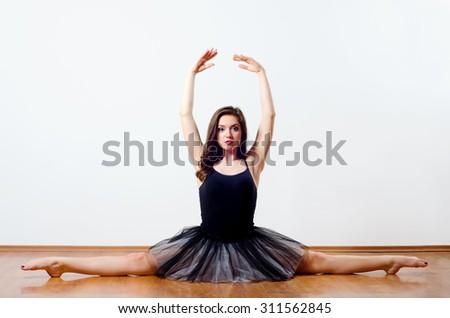 Beautiful ballet dancer performing split on the floor. - stock photo