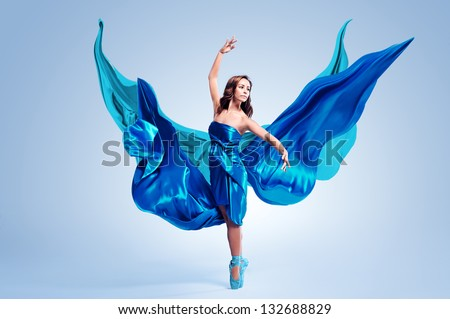 Beautiful ballet dancer with flowing blue fabric dancing with grace in studio - stock photo