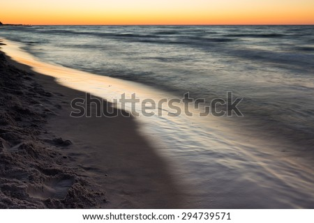 Beautiful Baltic sea beach at sunset. Beautiful seascape with sky reflected in water. - stock photo