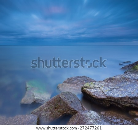 Beautiful Baltic sea landscape with stone breakwater. Tranquil long exposure landscape with moody blurred sky and water. - stock photo