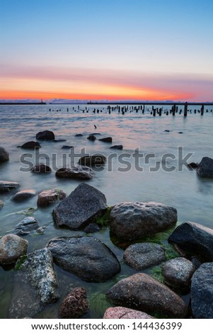 Beautiful Baltic sea sunset seascape with stones in foreground, old destroyed wooden pier and gate through harbor water breaker in background