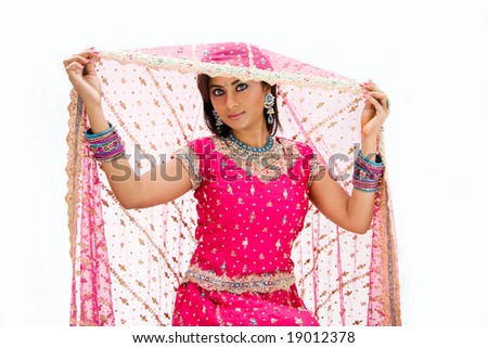 Beautiful Bangali bride in colorful dress and lifting her veil, isolated