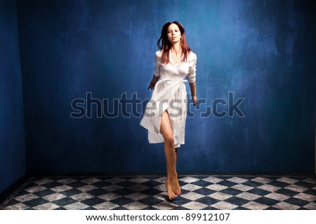 beautiful barefoot woman in white dress in motion in empty room - stock photo