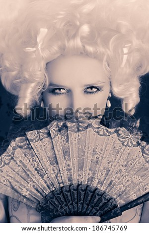 Beautiful Baroque Woman Monochrome Portrait with Wig and Fan - Baroque style portrait of a young beautiful woman behind a hand fan   - stock photo