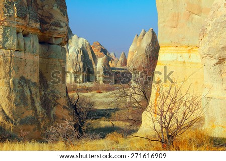 Beautiful barren landscape - ashen mountains (volcanic rocks) - eerie carved and hollowed out structures at the evening in Red Valley, Goreme, Cappadocia, Central Anatolia, Turkey - stock photo