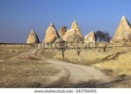 Beautiful barren landscape - winding country road through a field and ashen mountains - eerie carved geological structures at the evening in Rose valley, Goreme, Cappadocia, Central Anatolia, Turkey - stock photo
