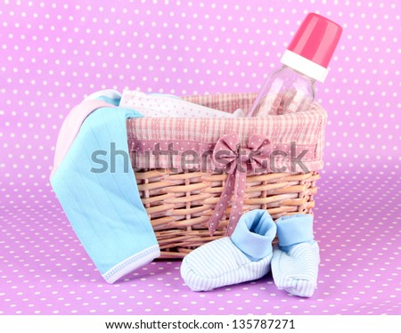 Beautiful basket of baby clothes on a pink background