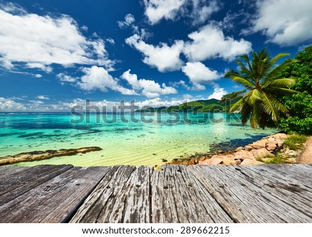 Beautiful beach and old wooden pier with palm tree at Seychelles, Mahe - stock photo