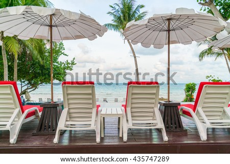 Beautiful beach chairs with umbrella around outdoor swimming pool neary sand and sea - stock photo