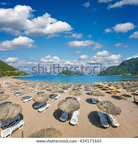 Beautiful beach in popular Turkish holiday resort town Icmeler. Empty beach loungers with umbrellas on beach at clear blue sea. - stock photo