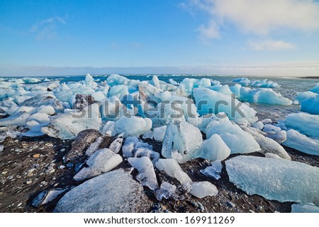 Beautiful beach in the South of Iceland with a black lava sand is full of icebergs from glaciers not far away. - stock photo