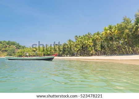 Beautiful beach of Ngapal with fisherman boat and palms hanging over the seai, Myanmar