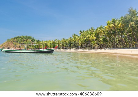 Beautiful beach of Ngapali with fisherman boat and palms hanging over the sea, Myanmar - stock photo
