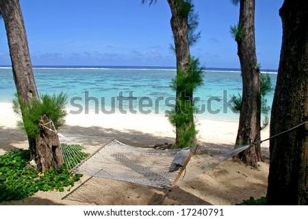Beautiful beach on a tropical island with a hammock - stock photo