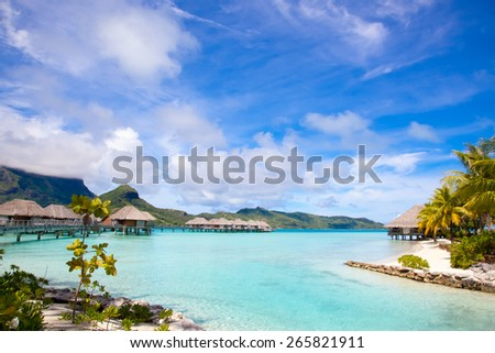 Beautiful beach on Bora Bora island in French Polynesia.  Thatched villas / bungalows over water.  White sandy beach and palm trees. - stock photo