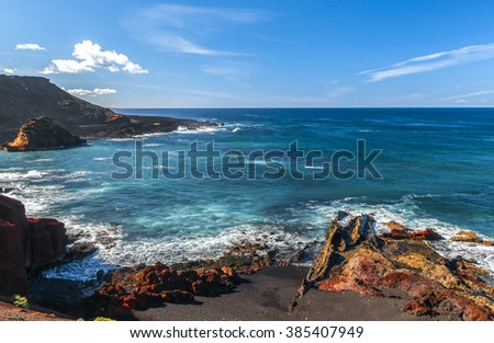 Beautiful beach on the Atlantic Ocean in the village of El Golfo. A rocky beach surrounded by volcanic mountains / El Golfo bay on the Atlantic Ocean. Lanzarote. Canary Islands - stock photo