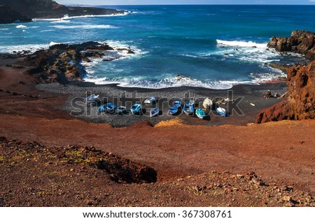 Beautiful beach on the Atlantic Ocean on the island of Lanzarote. A wonderful rocky beach with fishing and volcanic mountains / El Golfo bay on the Atlantic Ocean. Lanzarote. Canary Islands - stock photo