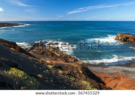 Beautiful beach on the Atlantic Ocean on the island of Lanzarote in El Golfo. A wonderful rocky beach surrounded by volcanic mountains / El Golfo bay on the Atlantic Ocean. Lanzarote. Canary Islands - stock photo