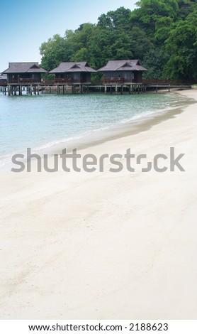Beautiful beach resort with white sandy beaches and water huts. - stock photo