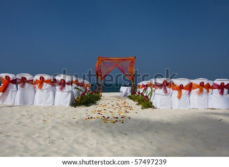 Beautiful beach scene set for a wedding ceremony with chairs, arbor, and flowers - stock photo