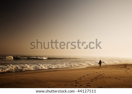 Beautiful beach with a surfer going to the waves early by the morning - stock photo