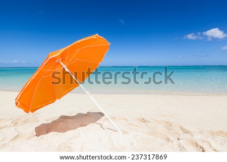 beautiful beach with an orange sunshade, turquoise sea, blue sky and white sand, Mauritius, Africa - stock photo
