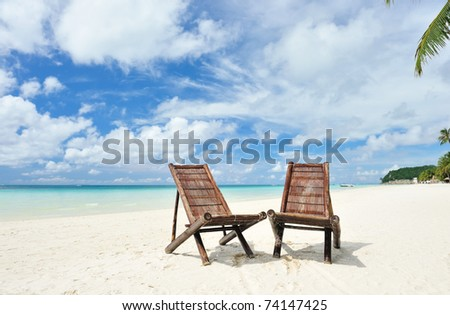 Beautiful beach with chaise lounge - stock photo