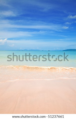 Beautiful beach with clear blue water and blue skies no a tropical island. - stock photo