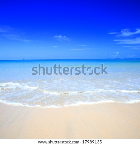 Beautiful beach with crystal clear blue waters  against blue sky - stock photo