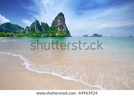 Beautiful beach with crystal clear blue waters of the Andaman sea against blue sky at Krabi bay, Thailand - stock photo