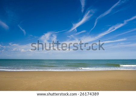 Beautiful beach with sand and waves with blue sky - stock photo