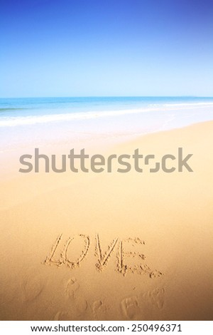 Beautiful beach with sand, blue waves and sky and text love - stock photo
