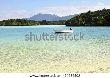 Beautiful beach with small islands and a boat. Shot in Okinawa, Japan. - stock photo