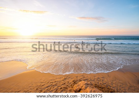 Beautiful beach with surfers swimming near El Cotillo village on Fuerteventura island in Spain - stock photo