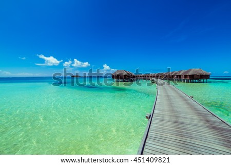 Beautiful beach with water bungalows and long jetty at Maldives. Summer travel holiday concept.