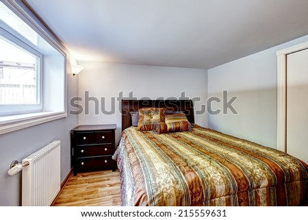 Beautiful bed with stripped brown bedding and nightstand in light blue room