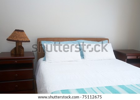 Beautiful bedroom interior with white sheets and bedside tables - stock photo