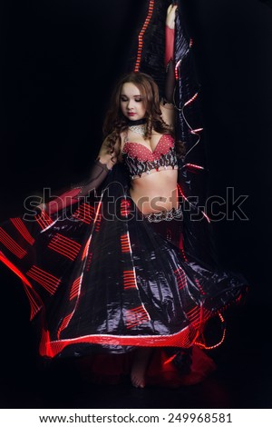 Beautiful belly dancer girl is wearing a black fashion costume. Isolated on black