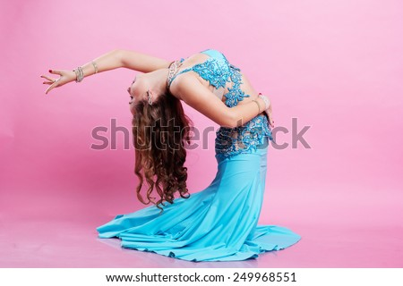 Beautiful belly dancer girl is wearing a blue fashion costume  - stock photo