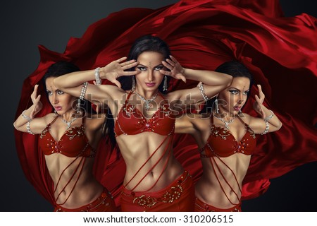 Beautiful belly dancer perfoming exotic dance in red flutter dress - stock photo