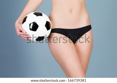 beautiful belly of a woman with a hand holding a soccer ball - stock photo