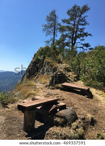 Beautiful bench seats on the hill in the mountains/blue sky on background