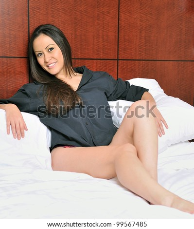 Beautiful bi-racial woman (Asian and Caucasian) resting in bed on pillows wearing only men's shirt - stock photo