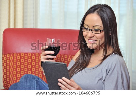 Beautiful bi-racial woman (Asian and Caucasian) resting on red chair holding a glass of red wine while looking at tablet computer - stock photo