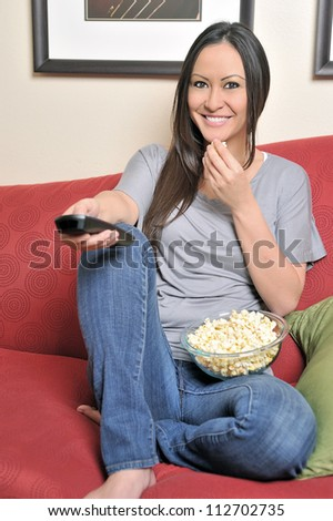 Beautiful bi-racial woman (Asian and Caucasian) resting on red couch holding a television remote control and a bowl of popcorn - healthy snacking - stock photo