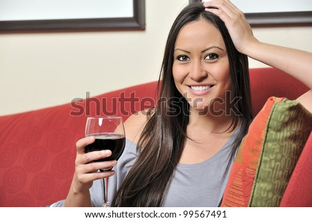 Beautiful bi-racial woman (Asian and Caucasian) resting on red sofa holding a glass of red wine - stock photo