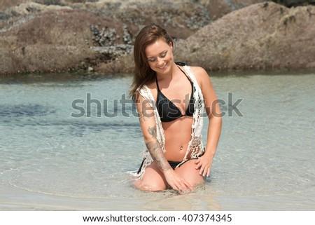 Beautiful bikini babe sitting in the sea playing with the water with copyspace - stock photo
